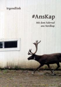 Von rechts läuft ein Rentier ins Bild entlang einer Fast weißen Holzwand, in der ein kleines, schmales Fenster ist. Auf dem Buchcover sind Titel Ans Kap und Untertitel Mit dem Fahrrad ans Nordkap zu lesen.