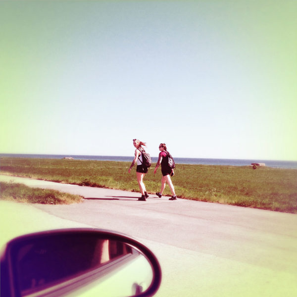 Blick aus dem Seitenfenster des Autos über den Spiegel hinweg auf zwei Passantinnen . Flachland an der Küste. Das Bild hat einen Siebziger Jahre Farbstich hellbläulich leicht vergilbt.