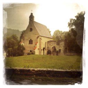 Ein von regnerischer Atmosphäre verdüstertes verwaschenes Bild einer Kapelle.