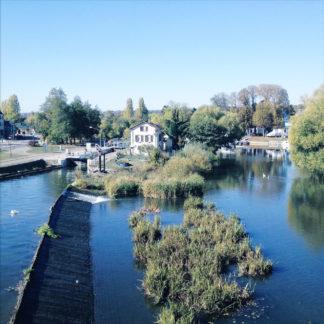 Bläuliches Bild von einer Brücke hinab auf einen Fluss. Ein Schleusenhaus und ein Stauwehr schmiegen sich an Uferbewuchs.