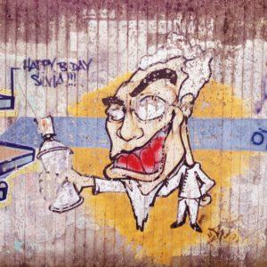 Eine gesprayte Karikatur mit weit aufgerissenem Mund an übergroßem Kopf auf winzigem Körper hält eine Spraydose in der Hand.