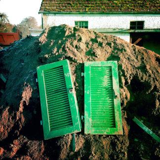 Zwei grüne, hölzerne Fensterläden liegen auf einem Erdhaufen vor einer Baustelle. Es sieht so aus, als könnte man sie öffnen und in den Erdhaufen hineinschauen.
