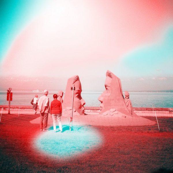 Ein rosa und hellblau verfärbtes Bild, das wie eine Ufolandung anmutet. Zwei Osterinselöhnliche Köpfe vor einem Seeufer werden von zwei Menschen eäugt, die nur etwa halb so groß sind wie die Sandskulpturen. Die Lichteinfälle wirken wie aus einem UFO-Film.