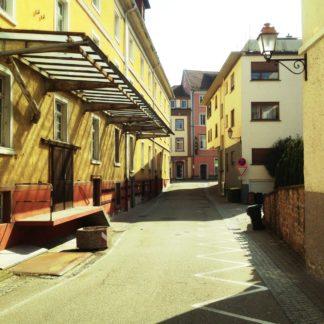 Blick in eine schmale Stadtstraße. Zur Linken eine überdachte Laderampe. Die Flucht nach Vorne lässt einen historischen Stadtkern vermuten.. Gelblich blasses Bild.