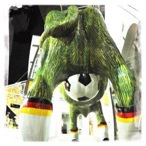 Blick underfoot auf den Hintern einer kunststoffenen Kuh. Das Euter ist ein Fußball. Sie trägt Socken mit Deutschlandfarebnbund. Ihr Körper ist grün.