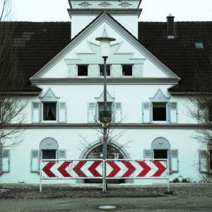 Expressionistisches Gebäude, weiß, viele Zacken, davor zwei rotweiße Baken, die die Symmetrie des Bildes verstärken.