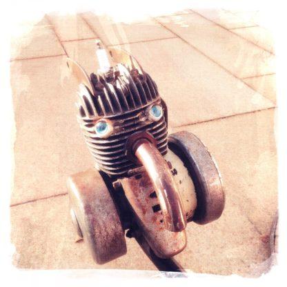 Ein Einzylindermotor auf blassbeigem Pflaster mit Rädern, der aussieht wie ein Kopf.