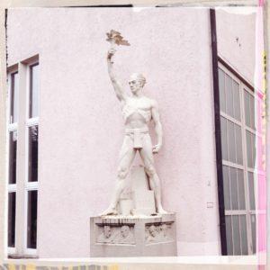 Blassrosa ist das verfremdete Bild eines Helden im Lendenschurz, der vor einer Hauswand auf einem Sockel steht. Er reckt mit der rechten Hand eine Art Fackel in die Höhe.