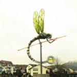 Eine Libellenskulptur auf einem Kreisverkehr. Die Flügel haben eine grünliche, durchschimmernde Färbung wie die Schaugläser von Libellen in Wasserwaagen.