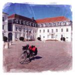 Bepacktes Reiserat mit schwarzen Seitentaschen und roter Gepäckrolle vor barockem Gebäude. Der Himmel ist blau. Das quadratische Bild hat eine Leinwand-Struktur.