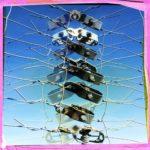 Eine senkrechte Reihe von Zaunspannern in dichter Lage sind gespiegelt übereinander gelagert. Underfoot-Aufnahme vor blauem Himmel. Das quadratische Bild hat einen rosa-gelben Rand.