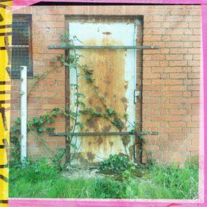 Eine rostende Stahltür in einer Backsteinwand ist mit zwei waagrechten Metallstreben verrammelt, von Efeu umrankt. Das quadratische Bild hat einen rosa Rand mit gelb-schwarzer Verzierung links.