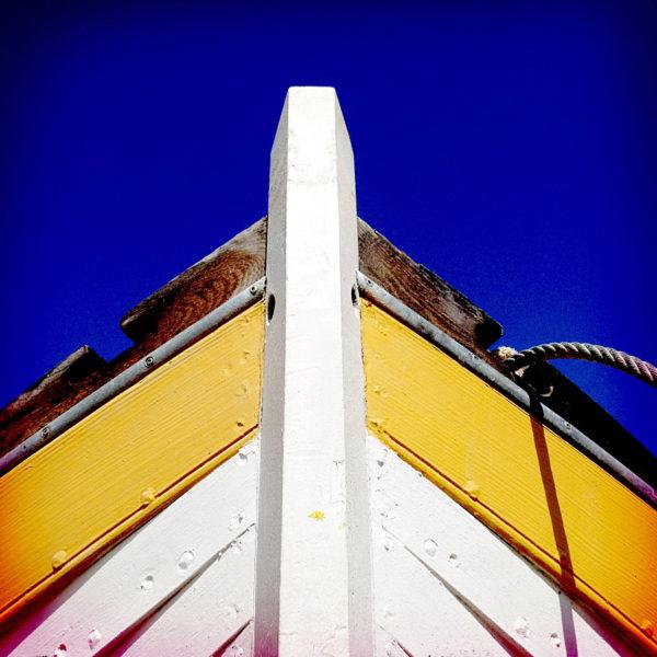 Bug eines Klinkerboots. Wie Fischgräten liegen die Planken übereinander. Gelb, weiß und braun unter tiefblauem Himmel.