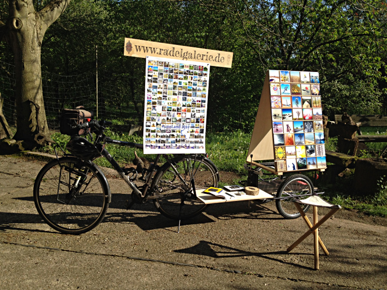Fahrrad mit Anhänger, auf dem ein fast zwei Meter hohes Display mit vielen kleinen quadratischen Bildern steht. Ein Schild mit der Aufschrift www.radelgalerie.de dient als Aufgängung für ein Plakat über dem Fahrradsattel