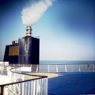 Blick über das bläulich schimmernde Stahldeck einer Fähre auf den weiß rauchenden Schornstein. Reling-Gekländer vor blau vignettiertem Himmel