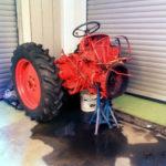 der hintere Teil eines Traktors. Man sieht die Hinterräder, das rote Gehäuse und das Lenkrad aufgestützt auf dreibeinigen, blauen Böclen über einer Pfütze vor heruntergelassenen Rollläden.