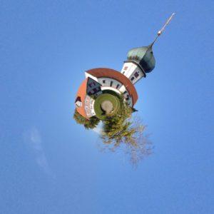 Ein sphärisch per Software zu einer Art Planet verformter Zwiebelkirchturm auf hellblauem Hintergrund.