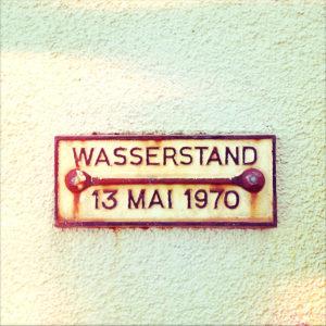 Ein gusseisernes, geprägtes Schild mit der Aufschrift Wasserstand 13 Mai 1970.