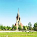 Reichlich verzierter Kirchturm ragt aus flachem Land in Cyanblauen Himmel. Das Grün junger Linden garniert die Friedhofsmauer.