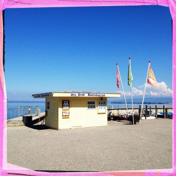 Kleines Fahrkartenverkaufshäuschen aus Brettern mit Flachdach. Schriftzug Urs Grob Bootsbetrieb. Rechts drei Fahnen, die wie ein Blumenstrauß gefächert sind. Das Bild hat einen rosa Rahmen, der den gesättigten blauen Himmel kontrastiert.