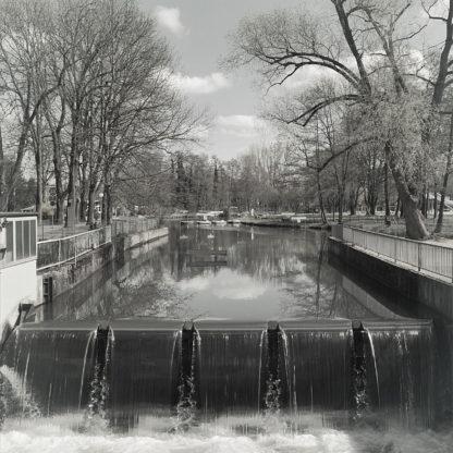 Schwarz-weiß-Aufnahme eines glänzenden Bachbetts, das über fünf Zungen geradlinig fällt. Rechts und links Geländer, Bäume, Quellwolken und ein paar Pontons im Hintergrund.