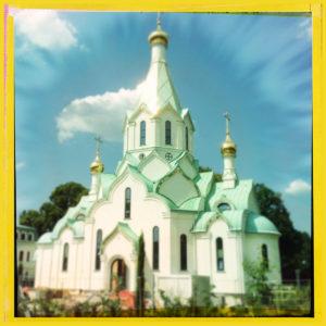 In einem gelben, quadratischen Rahmen erglänzt eine fast weiße Kirche mit goldenen Kuppeln, die aussieht wie ein Märchenschloss
