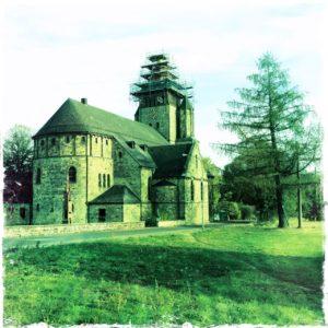 von der Rückseite blickt man auf ein Kirchenschiff. Das Bild ist grünlich verfremdet. Der Kirchturm ist von einem Gerüst umgeben. Neben der Kirche rechts steht ein Nadelbaum, der fast so hoch ist wie der Turm.