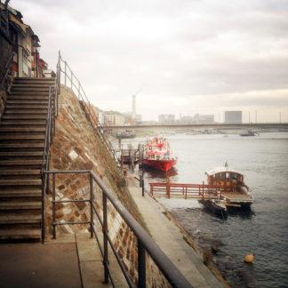 Links im Bild eine Treppe, die zum Ufer führt, an dem ein paar Boote verankert sind.