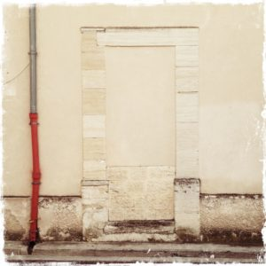 neben einer vermauerten Tür, in einer fast weißen Wand führt ein Regenfallrohr, das am unteren Ende markant rot ist.