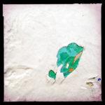 ein grünlicher Farbklecks schaut unter einer mehrfach abblätternden weißen Schicht hervor.