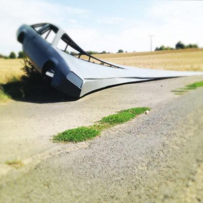Seitenteil eines Opel Manta, das mit einer stählernen Schwinge verschweißt auf einem abgeernteten Feld steht. Die Schwinge sieht aus wie der Flügel eines Teufelsrochens.