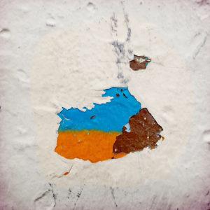 Nahaufnahme eines Farbkleckses, der unter abblätternder. weißer Farbe hervorschaur. Ein Hellblau über einem Gelborange, was mit viel guten Willens anmutet wie die Ukrainische Flagge. Daneben ein Akzent Rotbraun.