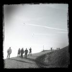 Entlang eines kargen, steilen Geländes führt ein ungeteerter Fahrweg, auf dem Menschen auf und ab laufen. In der Luft erkennt man schemenhaft zwei Gleitschirmflieger und Kondensstreifen. Das Schwarz-Weiß-Foto hat einen dicken, schwarzen Rand.