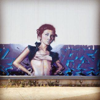 Mädchen mit knappem Top und in die Hüfte gestützten Armen vor Graffiti-Tags an eine Fabrikhallenwand gesprayt.