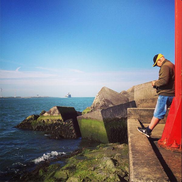 An einem roten Mast rechts im Bild lehnt ein Fotogrf mit Schirmmütze. Hinter Betonblöcken öffnet sich das Meer. Schiffe und Hafenanlagen am Horizont.