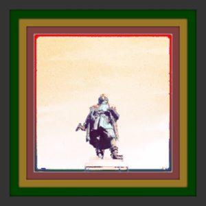 In einem mehrfach grau grün gold lila rot gerahmten Bild ist eine Abstrakte Figur, aus der Froschperspektive erkennbar.