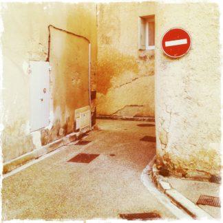 Blick in eine sehr enge Gasse, die einen abrupten Knick nach Links macht. Im rechten Teil des Bilds prangt ein Einfahrt verboten Schild.
