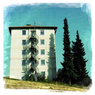 Ein fünfstöckiger Zweckbau mit Wendeltreppe neben Nadelbäumen. Die Schatten der Bäume und der Wendeltreppe liegen auf der hellen Fassade.