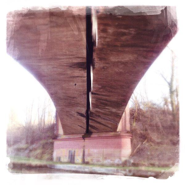 Unter einer braunen Eisenbahnbrücke erhascht man einen Blick auf den Fluss, das Ufergewächs und die Brückenkonstruktion. Durch Verfremdung wirkt das Foto wie ein Gemälde.