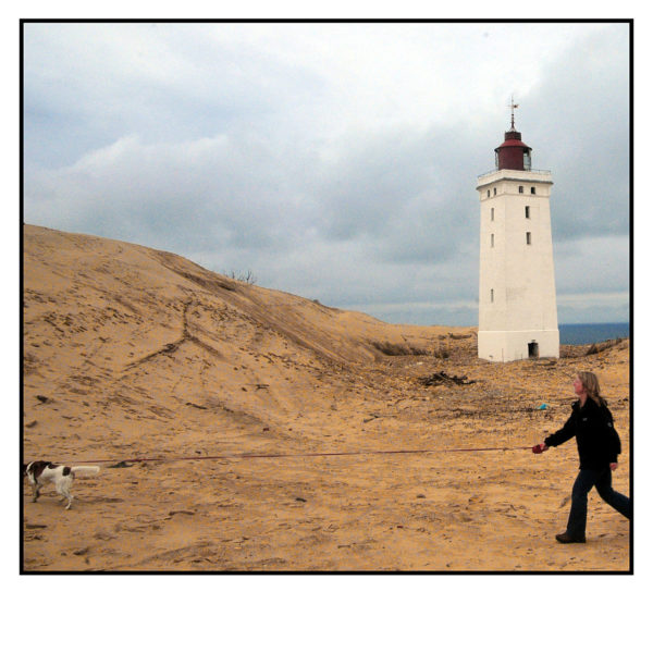 Im Vordergrund eines Leuchtturms zieht ein gescheckter Hund an gespannter Leine sein Frauchen hinter sich her.