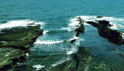 Blick von einer Klippe hinab auf Felsen und Brandung.