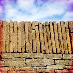 Eine kunstvoll aus gespaltenen, quaderförmigen Steinen aufgesetzte Mauer vor leicht bewölktem Himme.