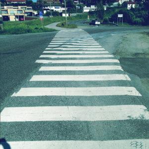 Ein Zebrastreifen zieht sich über verschiedene Arten von Teer auf eine Wohnsiedlung hin. Reifenspuren von Bremsungen und Beschleunigungen zieren das Weiß.