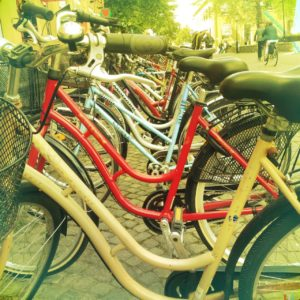 Nahaufnahme durch die Rahmen vieler Fahrräder, die aufgereiht an einem Fahrradparkplatz setehen. In dem gelblich verfärbten Bild sieht man rechts im Hintergrund Menschen und Radler.