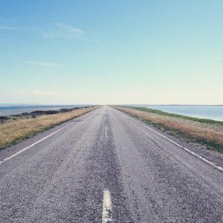 Schnurgerade Straße vom Mittesltreifen Richtung Horizont fluchtend. Rechts und links Meer und Marschland.