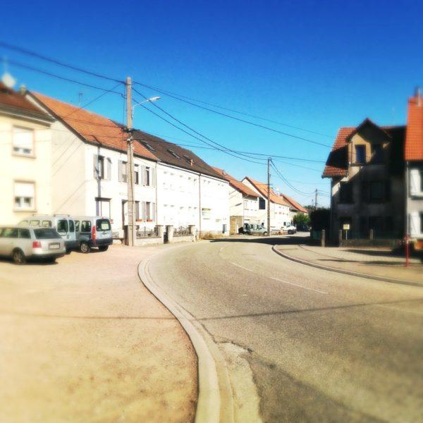 Der Blick folgt einem geschwungenen Bordstein auf großer Straßen- und Bürgersteigsfläche auf eine Zeile Arbeiterhäuser hin. Viele Oberleitungen durchziehen den tiefblauen Himmel.