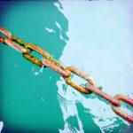 Eine rostige Kette führt schräg über grünlich schimmerndes Wasser