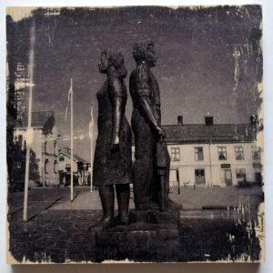 Rücken an Rücken stehen ein junger Mann und eine junge Frau auf dem Hauptplatz in der schwedischen Bergbaustadt Nora