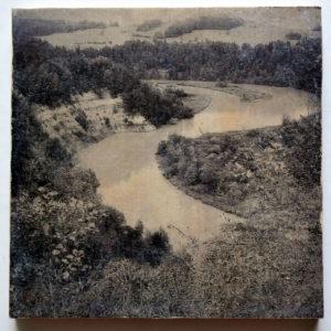 Wie ein spiegelverkehrtes S sieht der breite Fluss im engen Tal aus. Das Schwarz-weiß-Bild ist von erhöhter Position an einem Steilhang aufgenommen