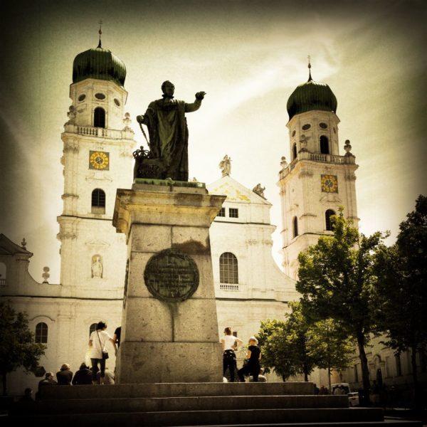 Schwarz-weiß Retro Bild des Passauer Doms, an dessen Front ein dunkles Denkmal steht. Eine Vignettierung rahmt das Bild. Zwei Kuppelkirchtürme, Bäume und Touristen.